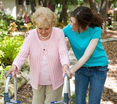 caregiver helping senior woman to walk