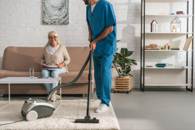 caregiver cleaning while senior woman watching