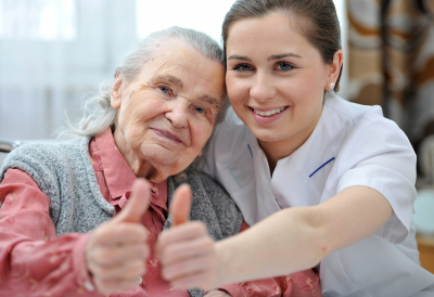 senior woman and female nurse showing thumbs up