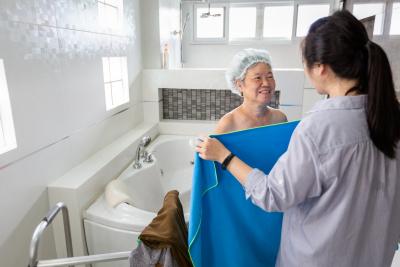 caregiver giving senior woman her towel after bath