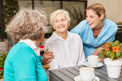 senior women and caregiver laughing