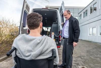 driver opening the door of a van to let senior man on wheelchair in